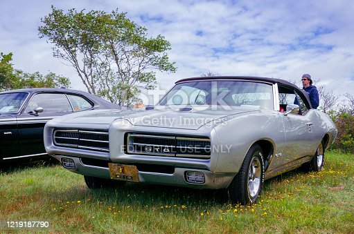 Chester, Nova Scotia, Canada - June 22, 2019 : 1969 Pontiac GTO convertible at Annual Graves Island Car Show at Graves Island Provincial Park, Chester, Nova Scotia Canada. A man wearing sunglasses stands behind the classic muscle car.
