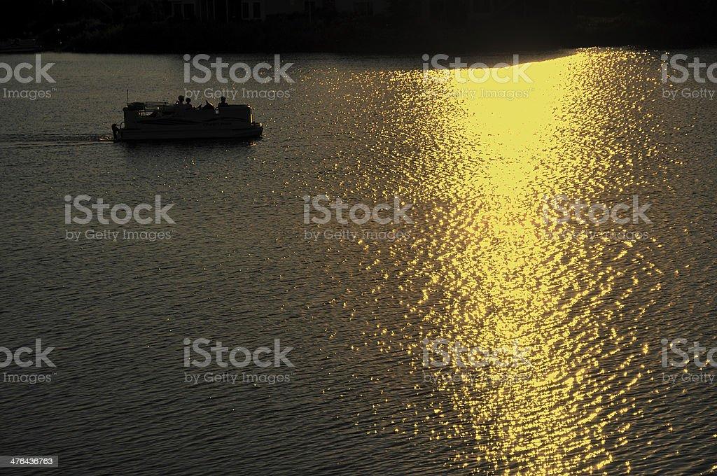 Pontoon Boat Motoring on Lake at Sunset stock photo