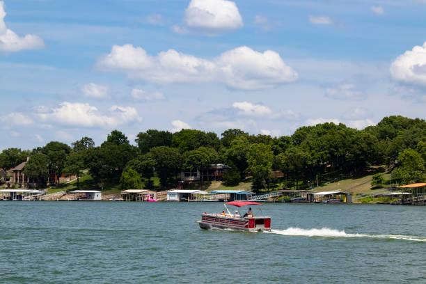 Bateau ponton automobile les dernières maisons et bateau accoste sur la rive par une journée ensoleillée au bord du lac - Photo