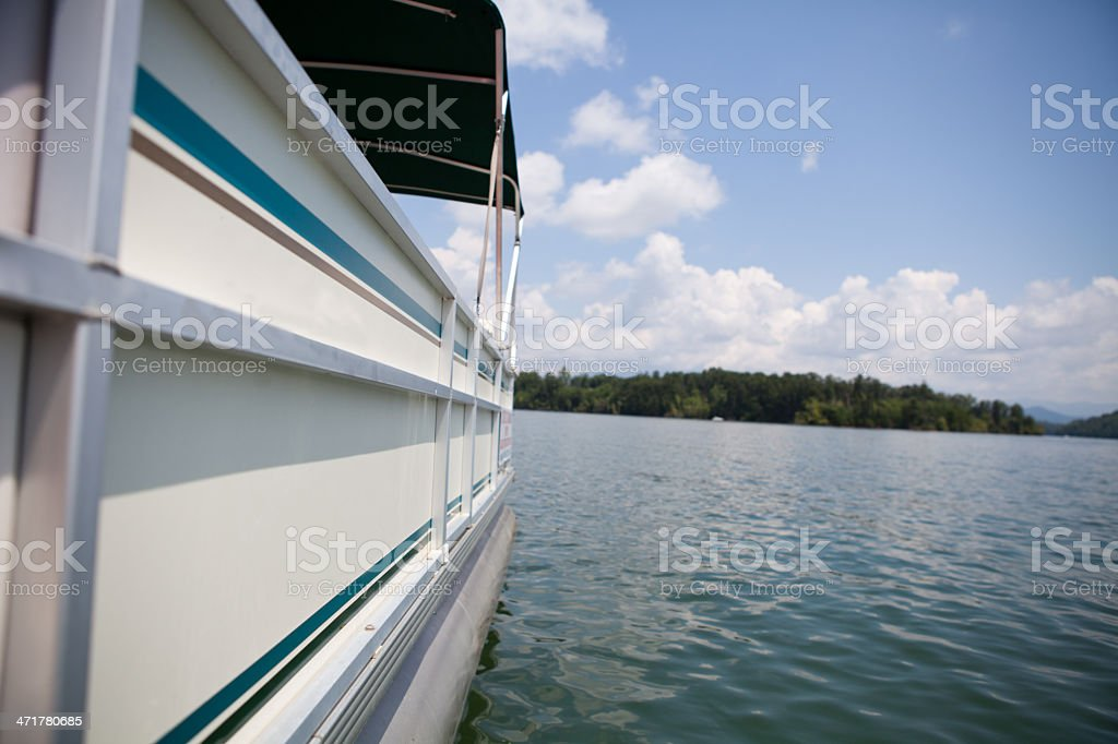 Pontoon boat on lake in the mountains stock photo