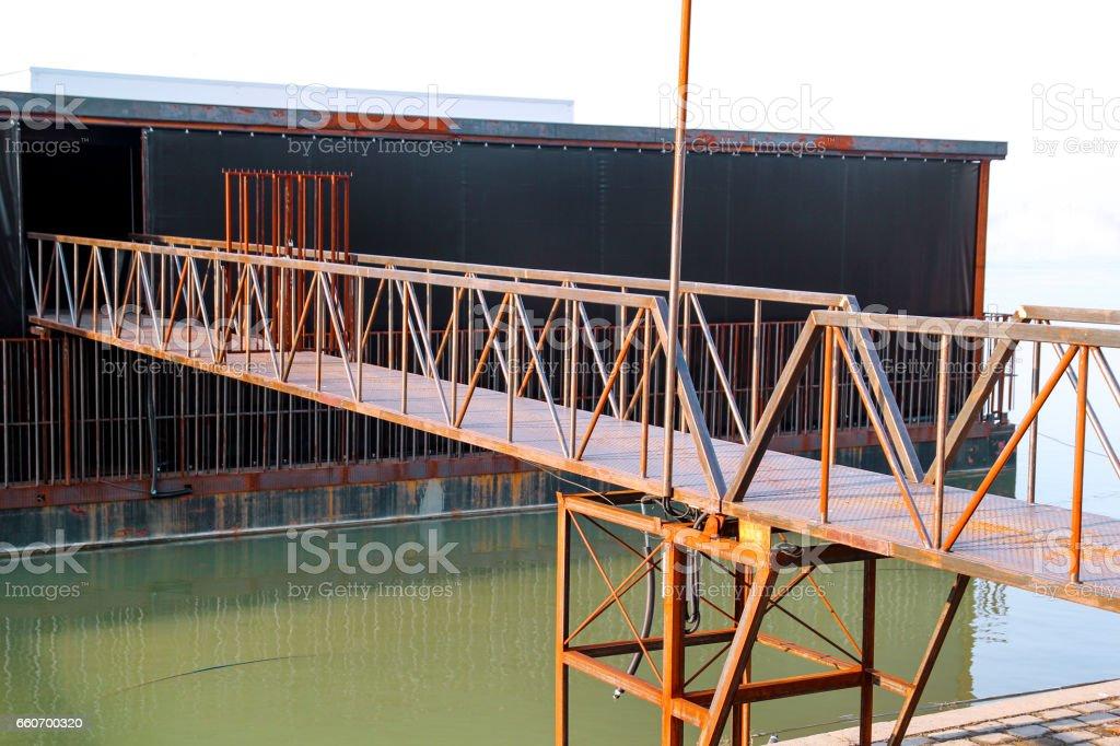 Pontoon bridge on raft. Old iron rusted pontoon bridge on raft on the river. Rustic architecture exterior raft on the river, close up. stock photo