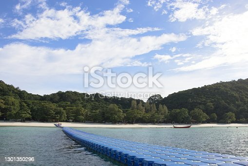 Plastic pontoon bridge walkway to white sand beach island with blue cloudy sky on background, Phuket city - Thailand.