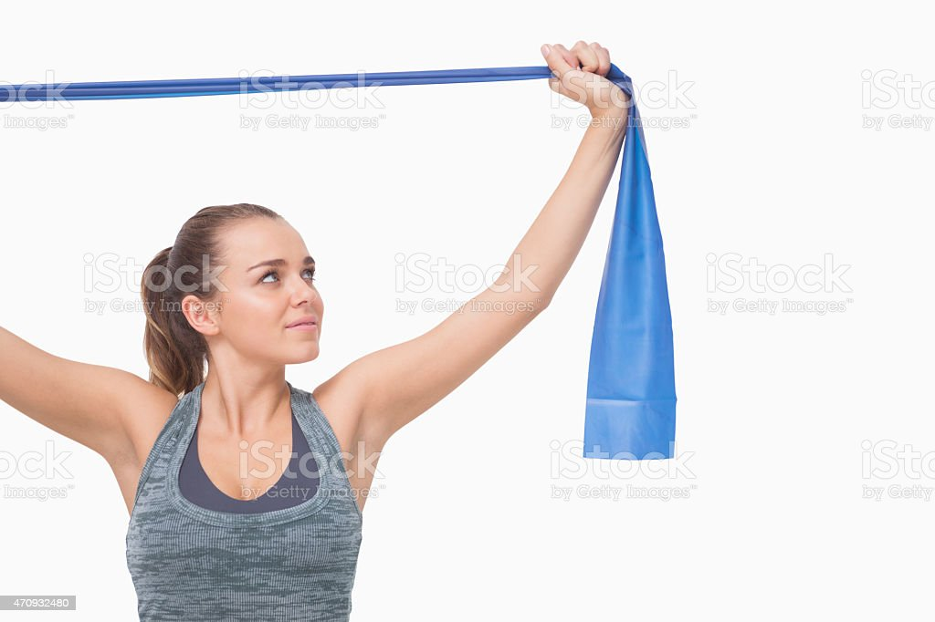 Ponytailed young woman training using a resistance band stock photo