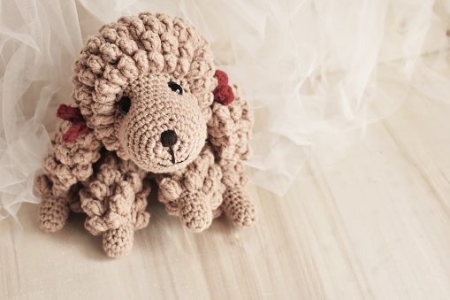 Poodle dog crochet handmade by brown soft wool. Vintage background with white chiffon theme and wood with pink pastel background. Creative handmade crocheting. Happy cute woolen pet toy for children. Puppy dog. Baby animal. Home decoration for bedroom of kids, teens and preschool, nursery