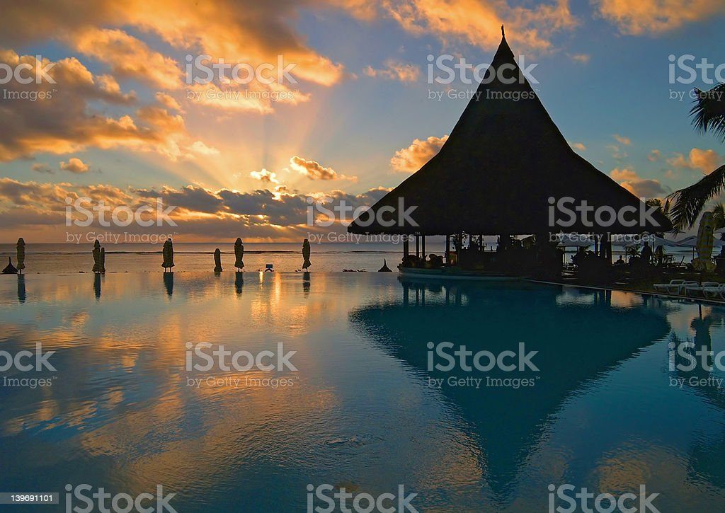 Pool and bar silhouetted against a spectacular sunset stock photo