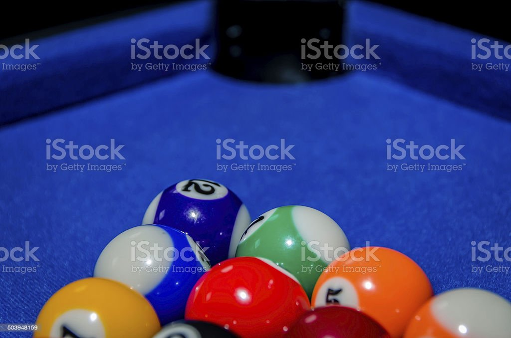 pool balls on pool table, colour image, with pocket at top of frame