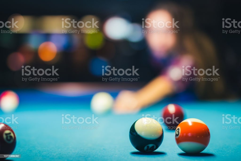 Selective focus shot of several pool balls with player in the...