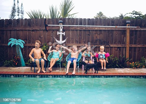 5 kids, cute and of varied ages, boys and girls, age 9, 8, 5 and 3 twin boys, sit at the edge of a domestic pool against a wooden fence in a backyard. Silly, playful, goofy kids making faces, looking full of joy and having a good time. They are all in swim suits and ready to jump in, just after the photo is taken. Summer, fun, and childhood, Siblings, cousins or friends sharing good times