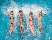 Four beautiful women splashing backwards into a pool. Perfect funny face expressions. Simply letting go. Nikon D3X. Converted from RAW. (XXXL)