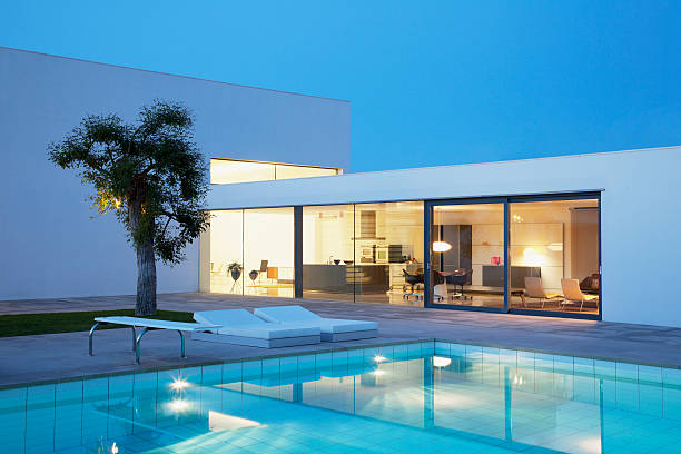 Pool outside modern house at night stock photo