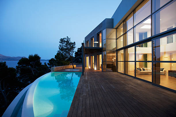 Pool outside modern house at twilight  infinity pool stock pictures, royalty-free photos & images