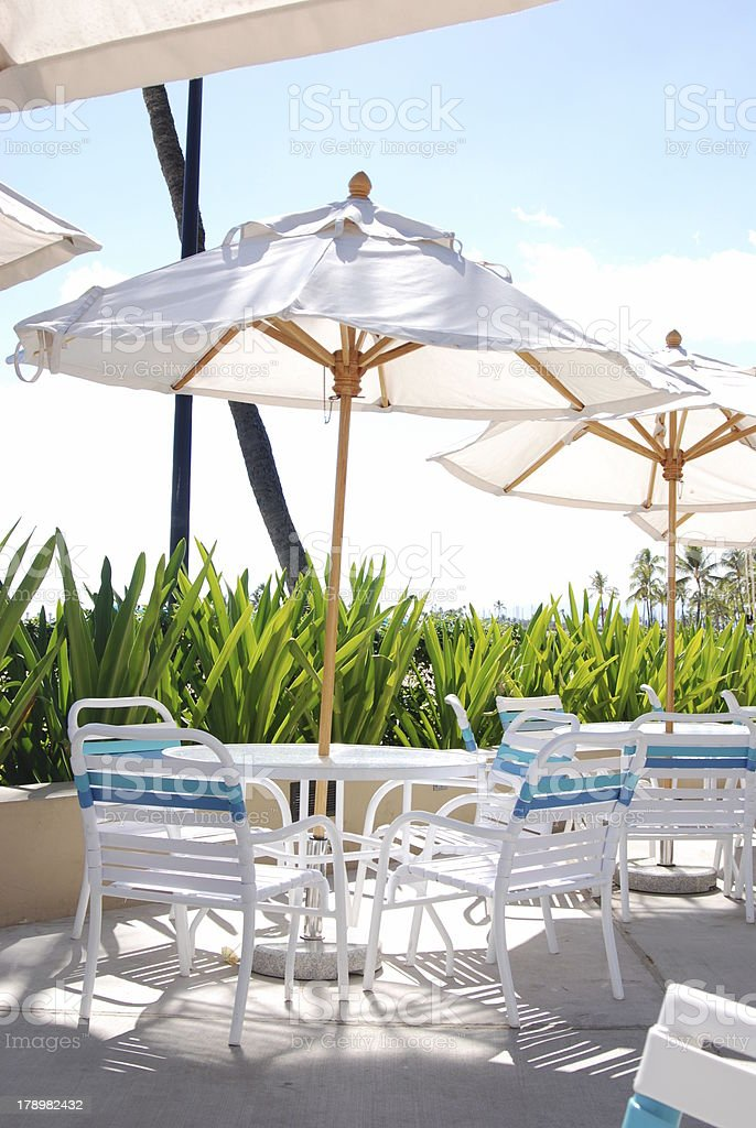 Pool Patio Chairs, Tables And Umbrellas Royalty Free Stock Photo