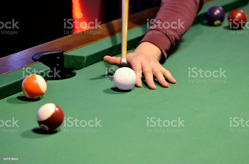 Close-up of pool player hits the cue ball