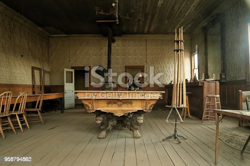 Bodie, California- July 15,2014: pool play room, lion-legged pool table in a ghost town, cable poles