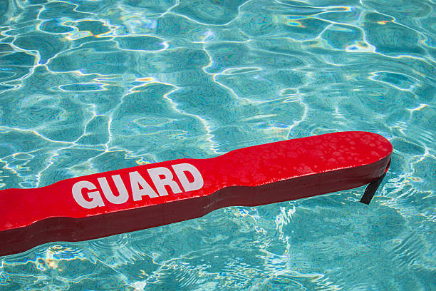 Pool Safe A close up shot of a life guards red rescue tube floating in a pool. lifeguard stock pictures, royalty-free photos & images