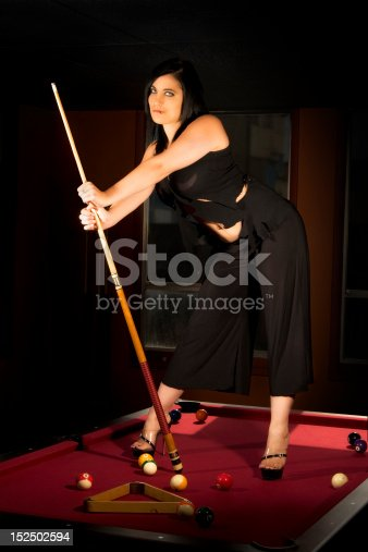 Incredibly hot model standing atop a red felt pool table holding a cue