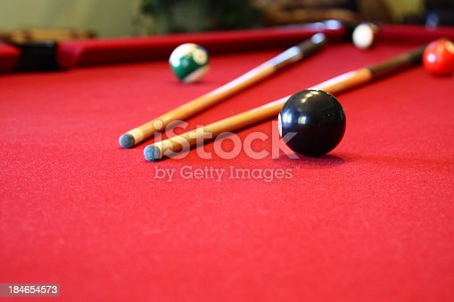 Two cues lie on a pool table beside the black '8-ball'.
