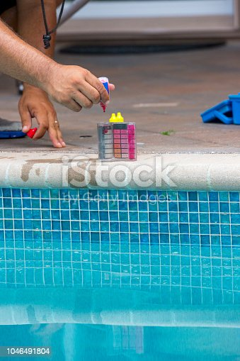 An unrecognizable man is using a pool testing kit to test the chemical levels in a   swimming pool. This is a standard kit used by pool maintenance people and homeowners to test the water to keep it healthy for swimmers. Shot with Canon 5D Mark lll.