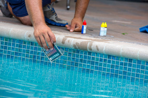 Pool testing kit being used in a swimming pool stock photo