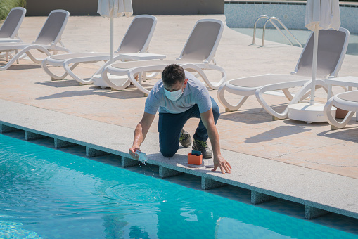 Pool testing kit being used in a swimming pool