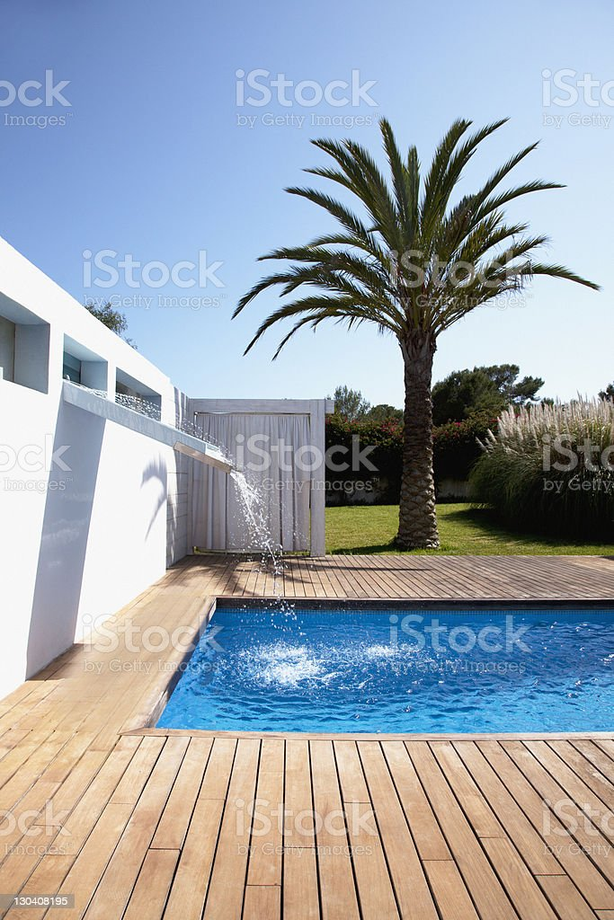 Pool with waterfall outside modern house stock photo