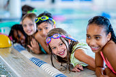 A multi-ethnic group of kids are indoors in a pool. Some of them are wearing goggles and smiling at the camera.
