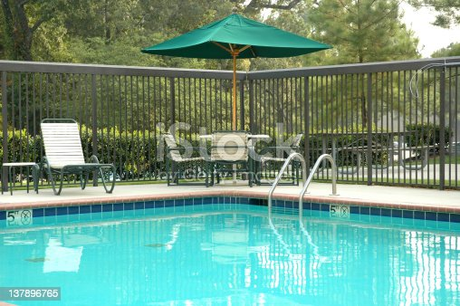 Peaceful poolside scene, with umbrella, table, and chairs.
