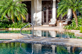 Beautiful pool with outdoor furniture in a tropical setting.