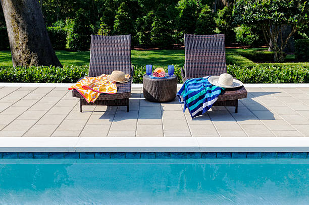 Poolside Setting with Refreshments and Lounging Tropical refreshments add to the leisure time at the the pool. poolside stock pictures, royalty-free photos & images