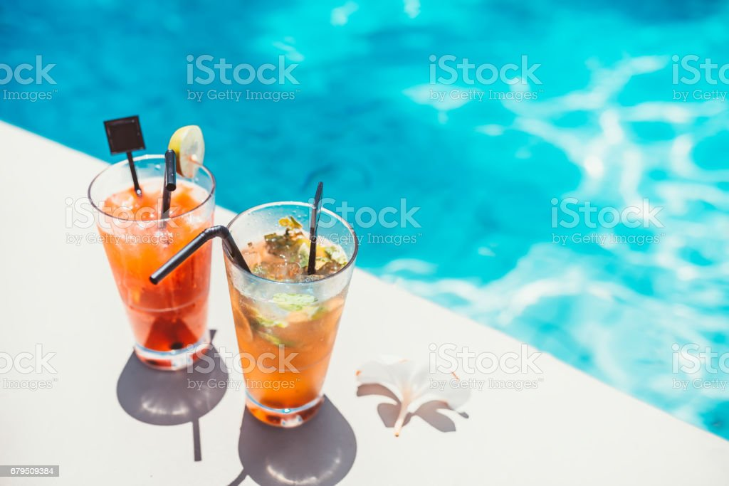 poolside symmetric cocktails served cold at pool bar with mojito and gin and tonic lemonade stock photo