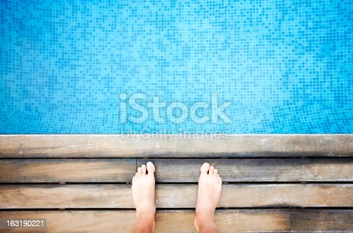 A swimming pool, wooden boarded edge, a man is standing preparing to jump in