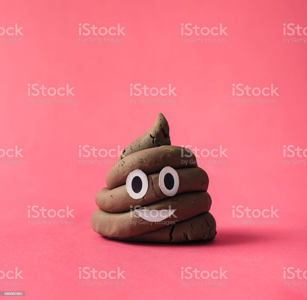Poop emoticon on pink background. stock photo