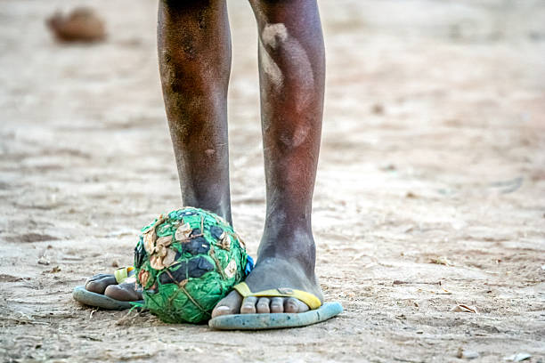 Poor african boy football stock photo
