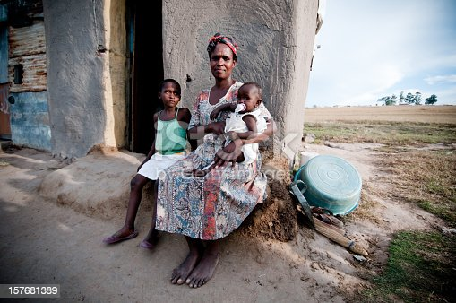Poor African family, mother with baby and little girl sitting outside their hut.