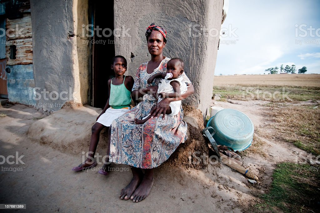 Poor African family sitting in front of a shanty hut stock photo