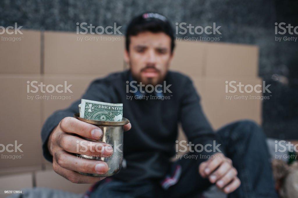 Homem pobre e sujo é sentar no chão e olhando na câmera. Ele está segurando um copo de metal com dólar nele. Ele tem que implorar ajuda e misericórdia - Foto de stock de Adulto royalty-free