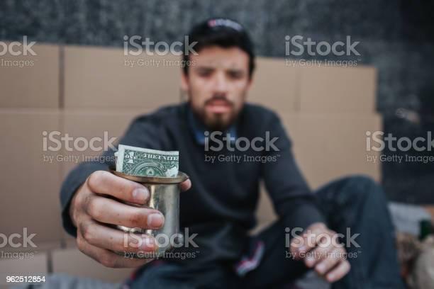 Foto de Homem Pobre E Sujo É Sentar No Chão E Olhando Na Câmera Ele Está Segurando Um Copo De Metal Com Dólar Nele Ele Tem Que Implorar Ajuda E Misericórdia e mais fotos de stock de Adulto