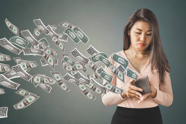 poor Asian woman holding  purse having problem with money flying away, over spending concept unhappy and poor Asian woman holding  purse having problem with money flying away, over spending concept background fee stock pictures, royalty-free photos & images