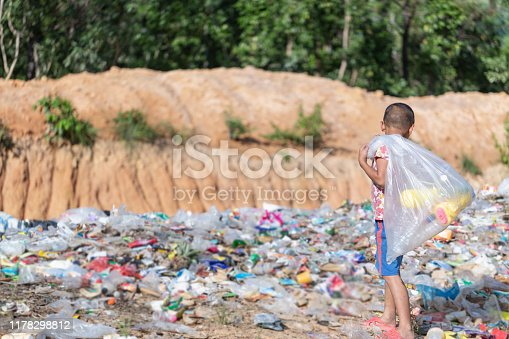 A poor boy collecting garbage waste from a landfill site in the outskirts. Poverty concept.