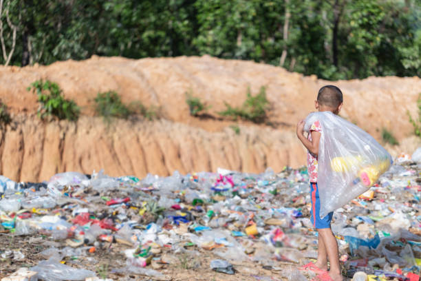 A poor boy collecting garbage waste from a landfill site in the outskirts. A poor boy collecting garbage waste from a landfill site in the outskirts. Poverty concept. poverty stock pictures, royalty-free photos & images