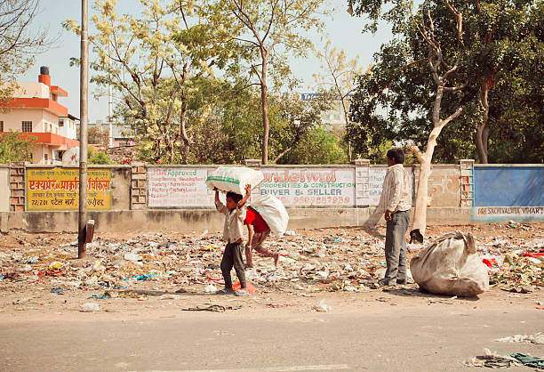 Poor children collect rubbish on streets for recycling Jaipur, India - January 21, 2015: Unidentified poor children collect rubbish on the streets for recycling on January 21, 2015 in Rajasthan. Jaipur, with population 6,664,000 people, is a capital of Rajasthan illiteracy stock pictures, royalty-free photos & images