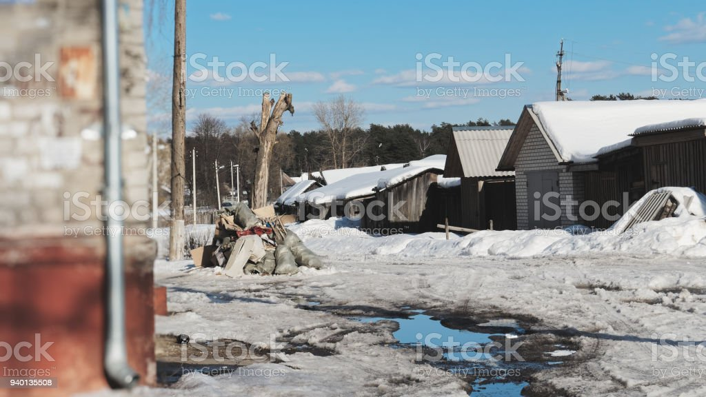 Poor countryside street in the end of winter. Melting snow and pools...