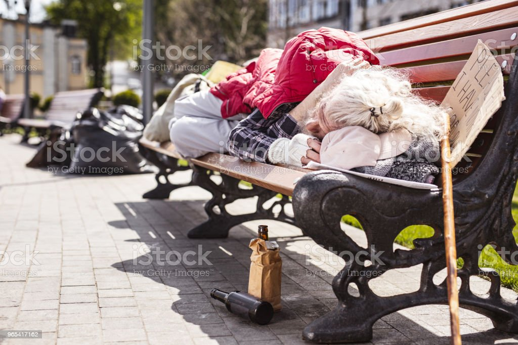 Poor elderly man living on the bench royalty-free stock photo