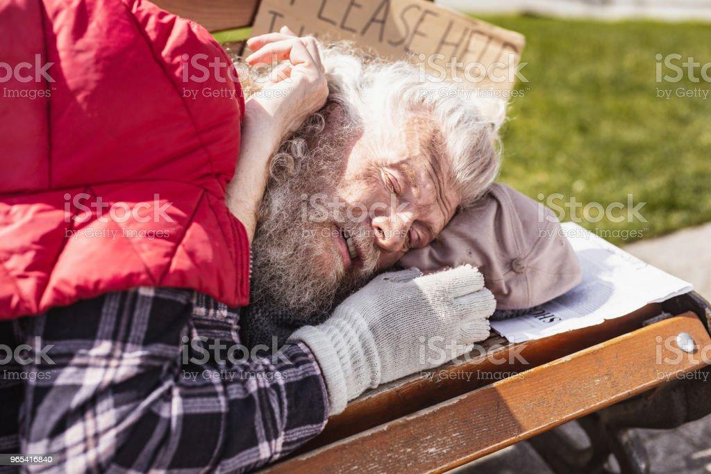 Poor elderly man sleeping on the bench royalty-free stock photo