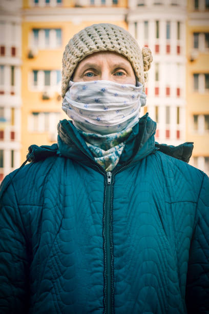 A poor elderly woman wears a homemade mask to protect herself from viruses stock photo