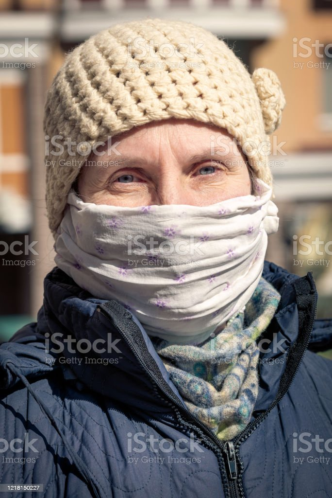 A poor elderly woman wears a homemade mask to protect herself from viruses A poor elderly woman wears a homemade mask to protect herself from viruses such as coronavirus, also known as covid-19, or SARS and MERS. She's in an urban environment Adult Stock Photo