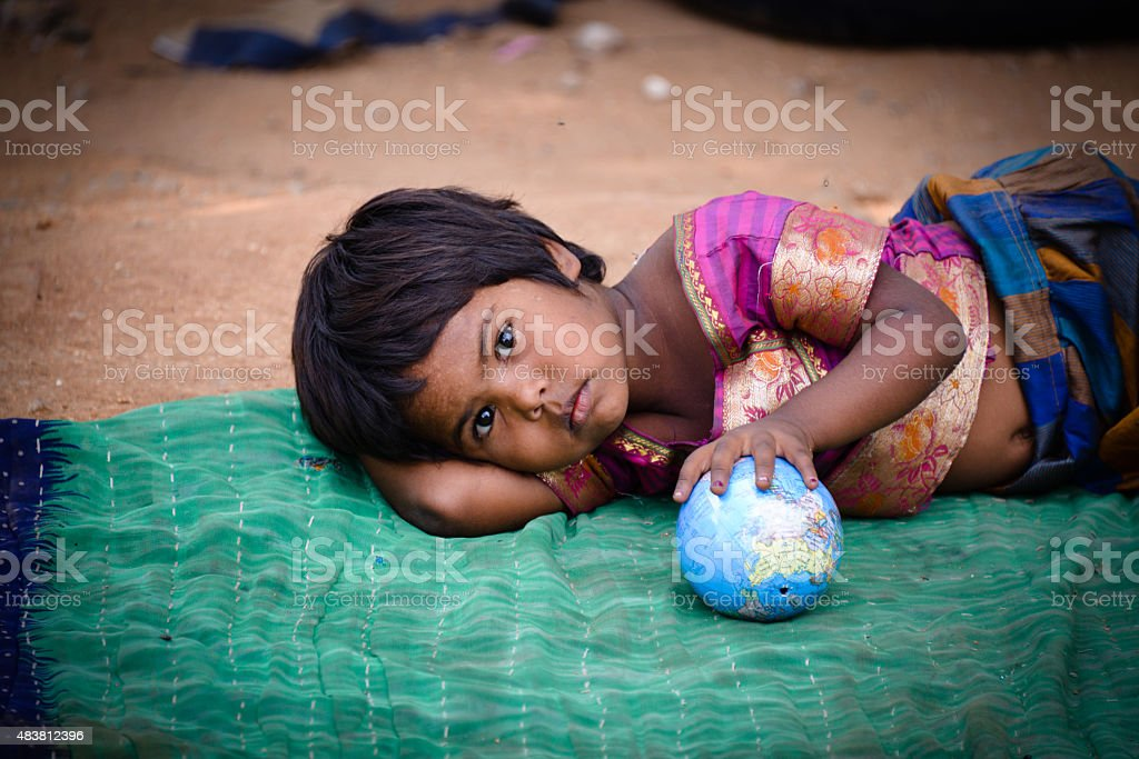 poor girl playing with globe stock photo
