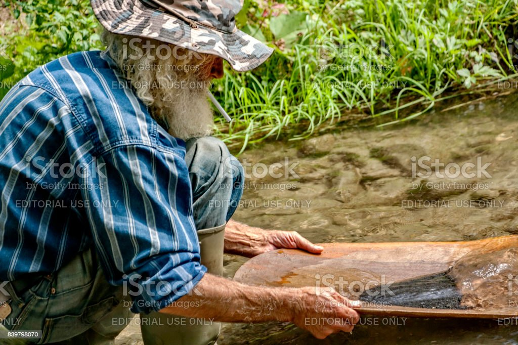 Poor gold washer searshing for gold in a creek stock photo