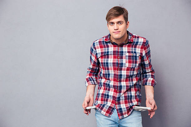 poor handsome young man in checkered shirt showing empty pockets - pocket stock photos and pictures