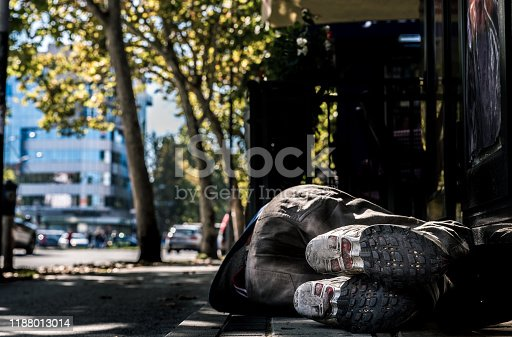 istock Poor homeless man or refugee sleeping on the concrete sidewalk floor ground on the urban street in the city, social documentary concept, selective focus 1188013014